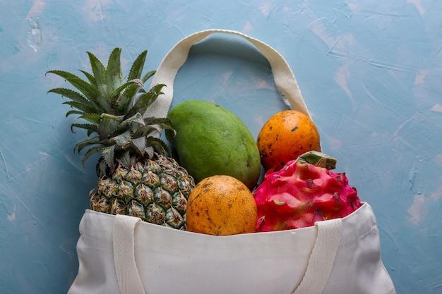 Concept zéro déchet, sac textile shopping avec fruits tropicaux frais: mangue, ananas, dragon et fruit de la passion sur fond bleu clair, orientation horizontale