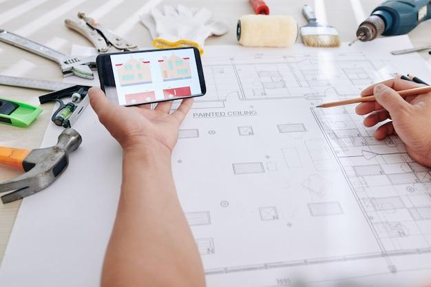 Concepteur comparant l'image de la maison avec le plan