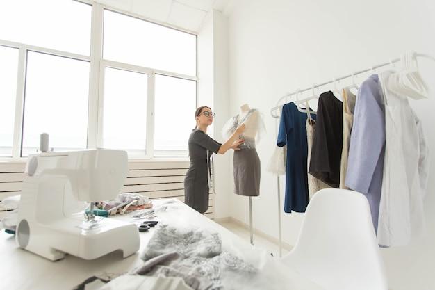 Concepteur couturier, créateur de mode et tailleur - le créateur décore la tenue sur le mannequin