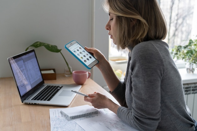 Concepteur de femme à l'aide de smartphone, prend une pause du travail et écoute l'orateur dans le clubhouse