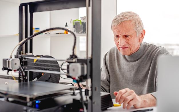 Concepteur d'homme adulte regardant une imprimante 3d pendant le processus de développement du travail