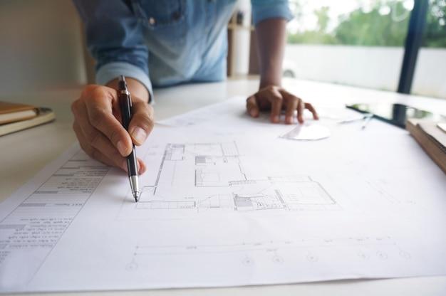 Concepteur d'intérieur de collègues planification de réalisation d'entreprise design sur le plan travail d'équipe concept avec compas