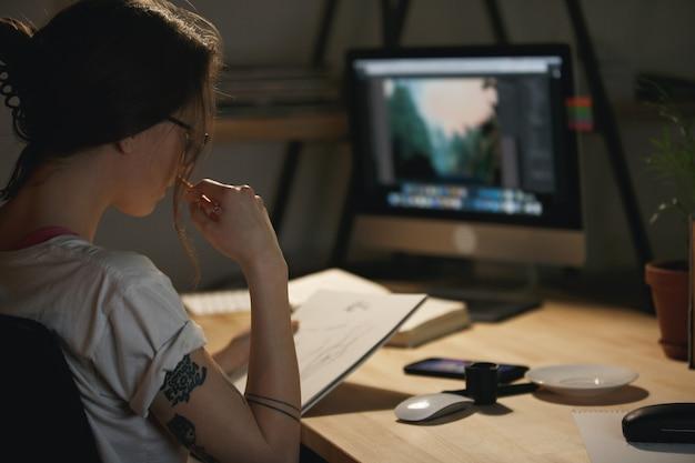 Concepteur de jeune femme concentré dessiner des croquis dans l'album