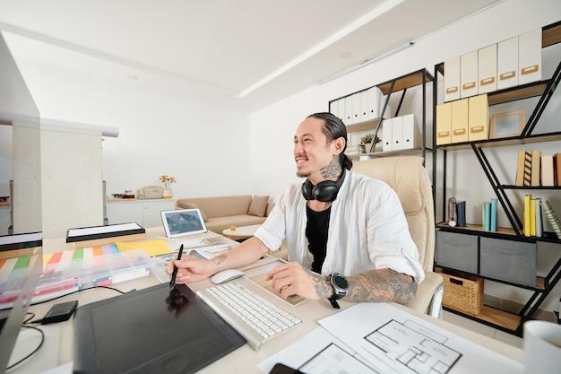 Concepteur de race mixte souriant à l'aide d'un stylo numérique lors du dessin de croquis pour le client à son bureau au bureau