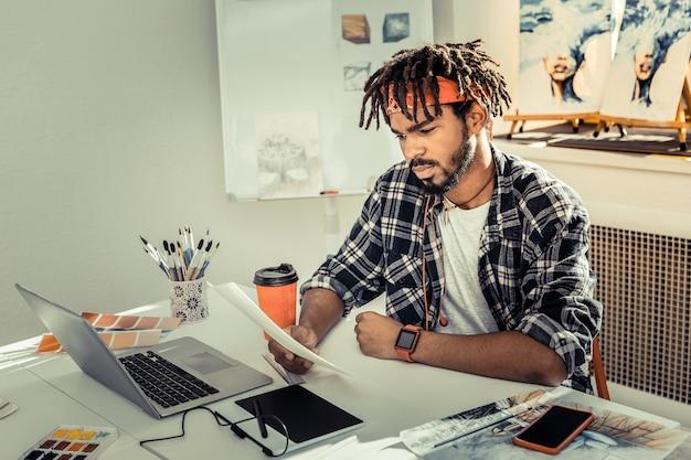 Concepteur réfléchi. jeune designer d'intérieur talentueux et prometteur se sentant attentionné tout en travaillant
