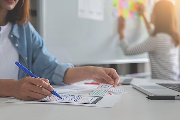 Concepteur de sites web faisant un brainstorming pour un plan stratégique.
