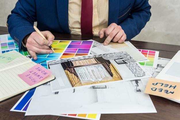 Concepteur travaillant avec un croquis de la maison et un échantillonneur de couleurs pour un intérieur moderne. projet d'archtercture, lieu de travail de bureau