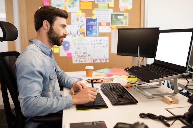 Concepteur utilisant un numériseur et un stylet sur un bureau créatif