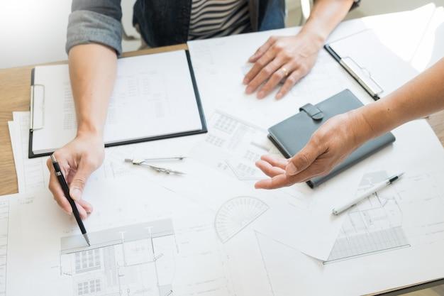 Les concepteurs du bureau travaillent sur discussion blueprint architect sur un nouveau projet. dessinez un travail d'équipe sur un bureau en bois.