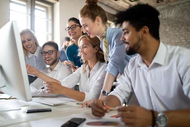 Des concepteurs souriants travaillant ensemble au bureau sur un ordinateur au bureau