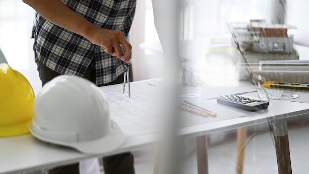 Les concepteurs utilisent des boussoles pour dessiner des dessins sur des plans de maison, des plans de maison et des casques de sécurité avec des outils de dessin sur la table.