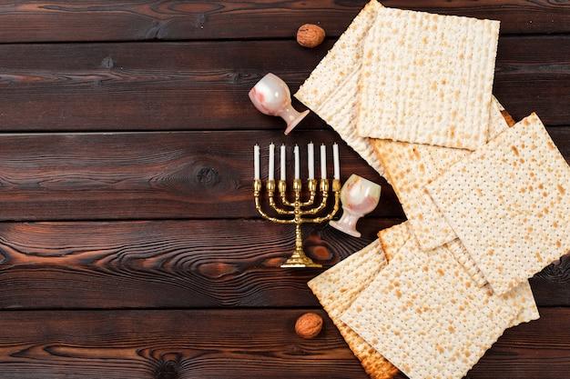 Conception de bannière de pâque juive avec du vin, du pain azyme sur une table en bois.