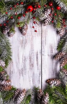 Conception de cadre de noël avec des pommes de pin couvertes de neige