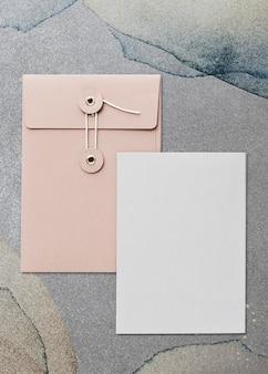 Conception de carte enveloppe rose pastel sur fond gris