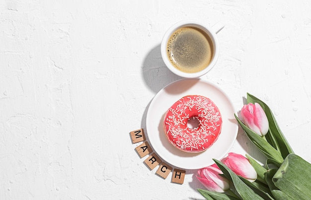Conception de carte de voeux du 8 mars avec une tasse de café et une soucoupe avec un beignet formant le numéro huit et une tulipe rose tendre à proximité