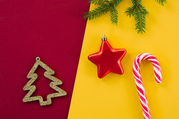 Conception de cartes de noël sur un fond coloré lumineux. arbre de noël doré créatif, branche d'épinette, canne en bonbon à la menthe et jouet d'arbre de noël. copyspace. décor de noël