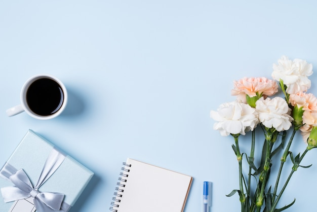 Conception concpet de voeux de fête des mères avec fleur d'oeillet, idée de cadeau de vacances et carnet de notes sur fond de bureau mères