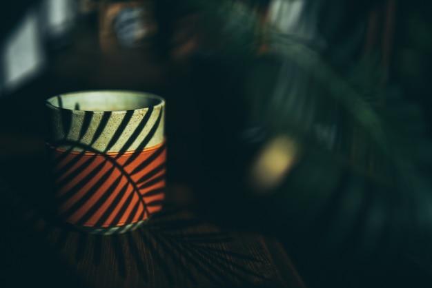 Conception de décoration végétale sur fond de style minimal, tasse de boisson sur un espace de table en bois naturel, intérieur moderne de mur vert dans une salle de cafés à la maison, boisson chaude et lumière du soleil le matin
