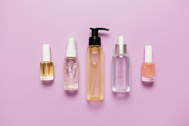 Conception d'emballages de cosmétiques biologiques. mise à plat, flacon pompe en verre transparent vue de dessus, pot de pinceau, pot de sérum hydratant sur fond violet. spa cosmétiques naturels