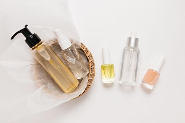 Conception d'emballages de cosmétiques biologiques. mise à plat, vue de dessus, flacon pompe en verre transparent, pot de brosse, pot de sérum hydratant dans une corbeille à papier sur fond blanc. spa cosmétiques naturels