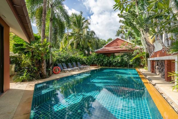 La conception extérieure de la maison, de la maison et de la villa avec piscine comprend une piscine, une terrasse, un jardin paysager et un lit de bronzage
