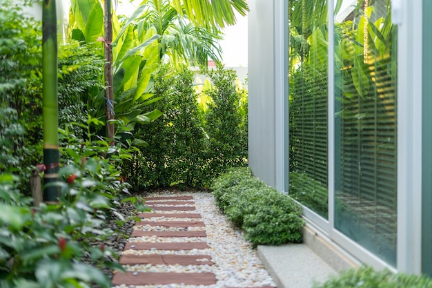 La conception extérieure de la maison de villa et de la maison présente un paysage et un jardin verdoyant à côté de la maison