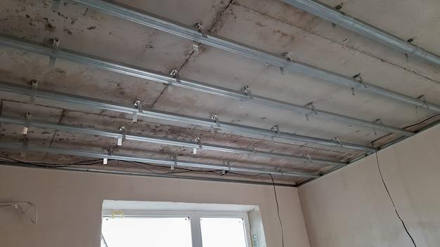 Conception de faux plafond, avant d'installer des cloisons sèches. plafond en plaques de plâtre d'une maison sur un chantier de construction, installation d'un faux plafond dans une pièce carrée.