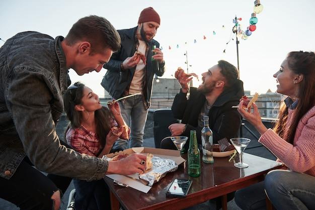 Conception de fêtes. manger de la pizza à la fête sur le toit. les bons amis ont le week-end avec de la nourriture délicieuse et de l'alcool