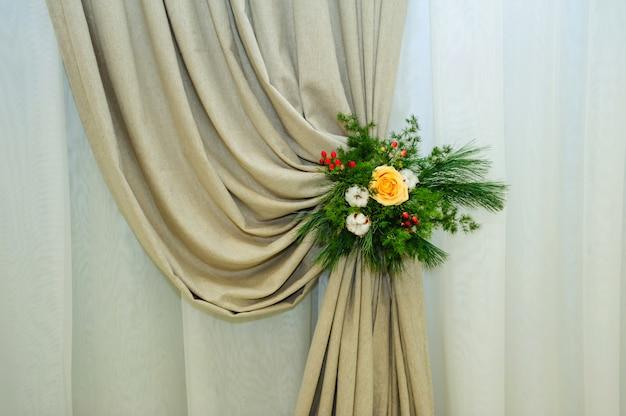 Conception florale originale de roses jaunes et de brindilles vertes sur la draperie, gros plan. décorations florales pour une célébration de mariage.