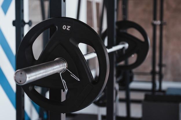 Conception de la force. barbell noir sur le support métallique dans la salle de sport pendant la journée. pas de monde autour