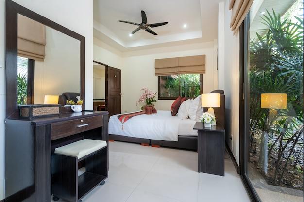 La conception intérieure de la maison, de la maison, du condo et de la villa comprend un lit double, un chemin de lit rouge et une coiffeuse dans la chambre