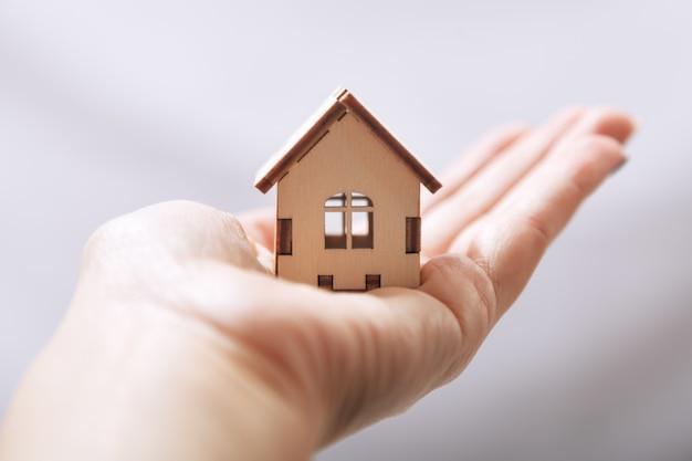 Conception de maison en bois miniature sur la paume, concept d'entreprise dans l'immobilier et de l'immobilier