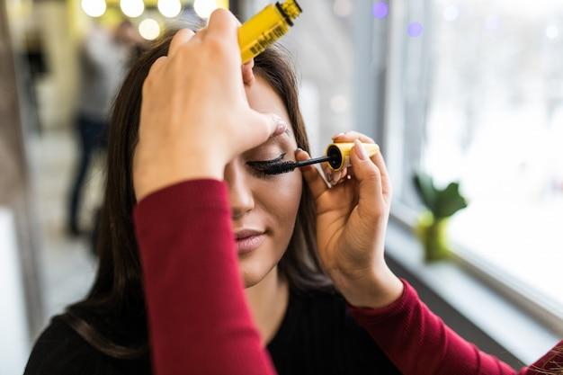 Conception de maquillage des paupières pour le joli modèle aux cheveux longs dans un salon de beauté