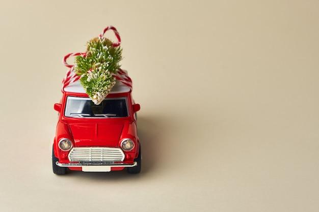 Conception minimale pour célébrer la carte de voeux de noël ou du nouvel an. concept de livraison de cadeaux. petite voiture jouet rouge et arbre de noël sur fond clair