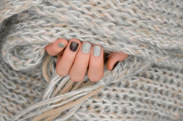 Conception d'ongle gris. main féminine avec manucure de paillettes.