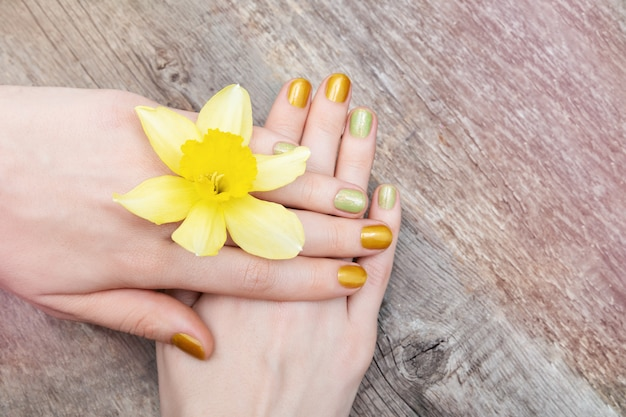 Conception d'ongle jaune. main féminine avec des paillettes manucure tenant des fleurs de narcisse.