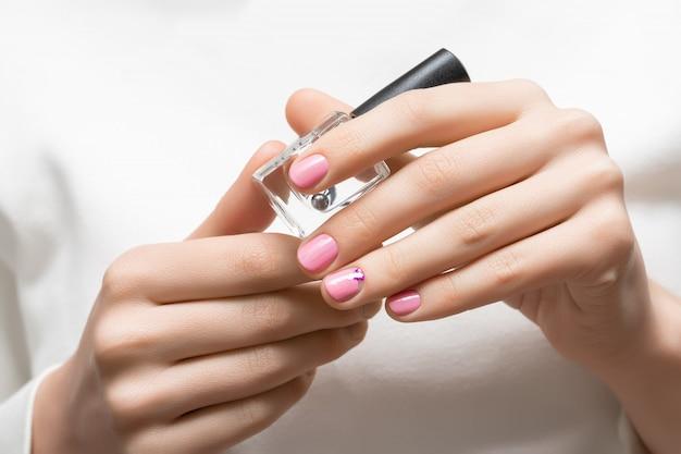 Conception d'ongle rose. main féminine avec manucure de paillettes.