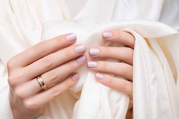 Conception d'ongle rose. mains féminines avec manucure paillettes.
