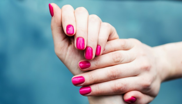 Conception d'ongles. mains avec manucure d'été rose sur fond gris. gros plan des mains féminines. art nail.