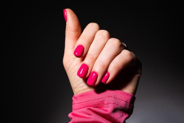 Conception d'ongles. mains avec manucure d'été rose sur gris
