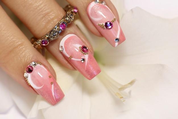 Conception d'ongles à la mode avec des strass sur un revêtement de vernis à ongles rose et blanc sur une main de femme