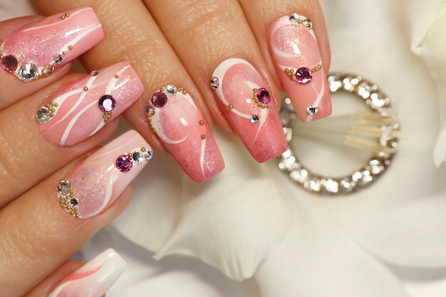 Conception d'ongles rose clair avec des lignes blanches, des strass, des paillettes avec des glaïeuls.