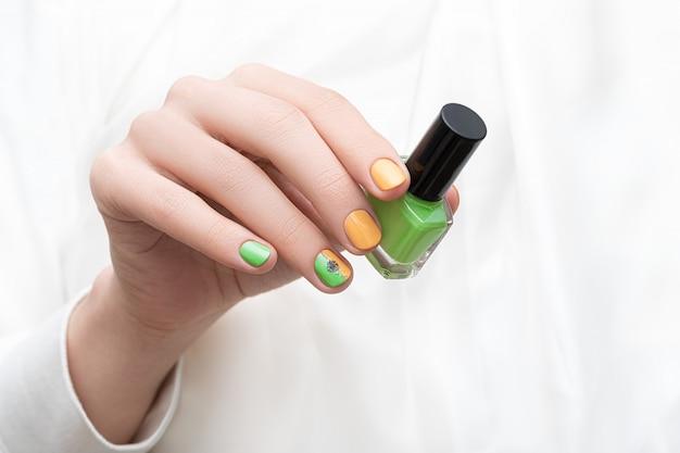 Conception d'ongles verts. main féminine avec nail art pissenlit.