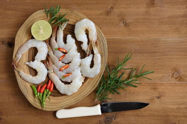 Conception à plat, crevettes crues, citron vert, piment et céleri, tomate et romarin sur plateau en bois sur bois, ingrédient épicé thaïlandais