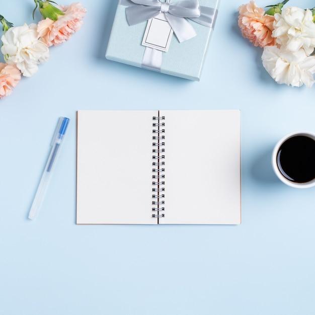 Conception de la salutation de la fête des mères avec fleur d'oeillet, idée de cadeau de vacances et agenda de cahier sur fond de bureau de la mère.