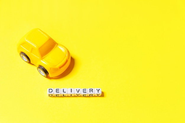 Conception simple voiture jouet jaune et inscription livraison mot isolé sur fond coloré jaune