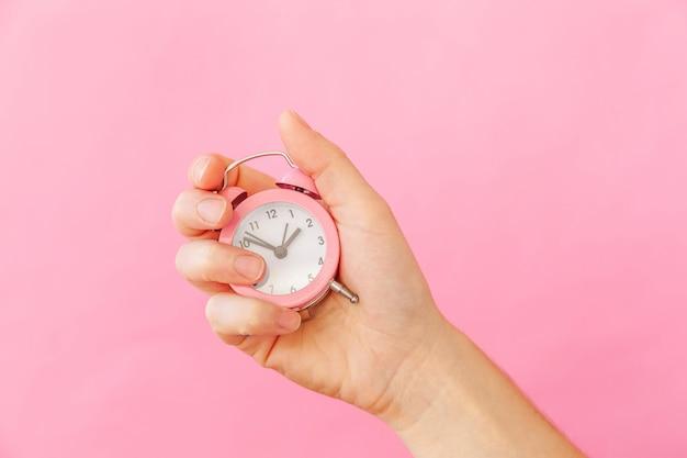 Conception simplement femme femme main tenant sonnerie double cloche réveil isolé sur fond tendance coloré pastel rose