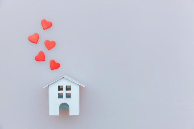 Conception simplement minimale avec maison jouet miniature blanche avec coeur rouge isolé sur blanc