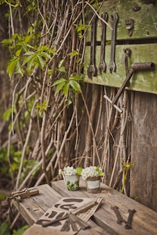 Conception de la zone de photo dans un style rustique, vieilles portes et planches en bois avec outils et fleurs printanières.