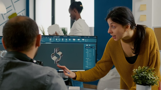 Conceptrice industrielle discutant avec un ingénieur technicien travaillant dans un programme de cao concevant d pro...